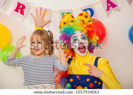 clown girl on the birthday of a child. A party for a child. Emotional Child fools around #1057934063