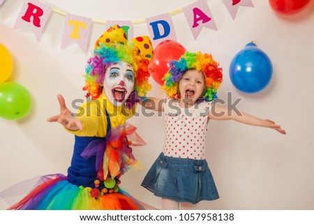 clown girl on the birthday of a child. A party for a child. A child in a clown wig #1057958138