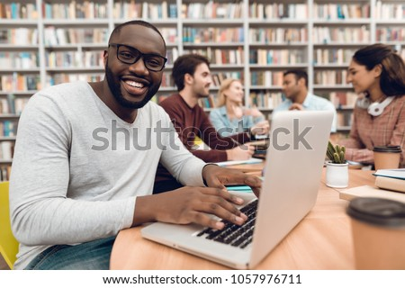 Group of ethnic multicultural students sitting at table in library. Black guy on laptop.
