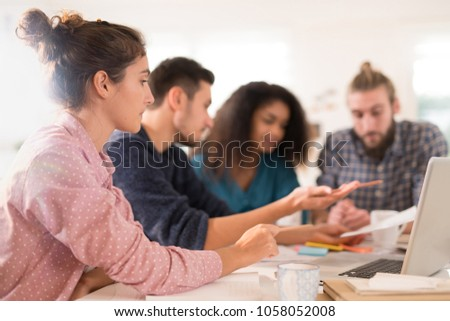 In the office. Meeting around a table, a young multi-ethnic team exchanges ideas on a new project. #1058052008