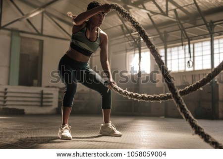 Fitness woman using training ropes for exercise at gym. Athlete working out with battle ropes at cross gym. #1058059004