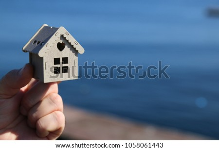 real estate and mortgage invesment. man holding house in his hand #1058061443