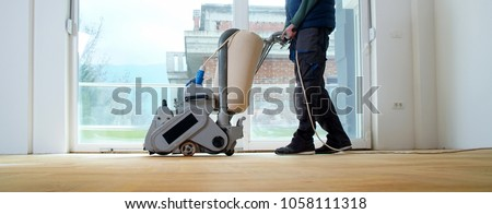 Sanding hardwood floor with the grinding machine. Repair in the apartment. Carpenter doing parquet wood floor polishing maintenance work by grinding machine Royalty-Free Stock Photo #1058111318