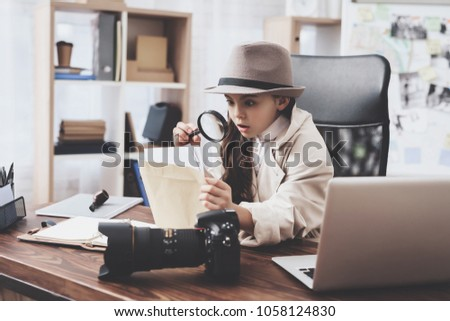 Private detective agency. Little girl in cloak and hat is sitting at desk looking at photos with magnifying glass. Royalty-Free Stock Photo #1058124830