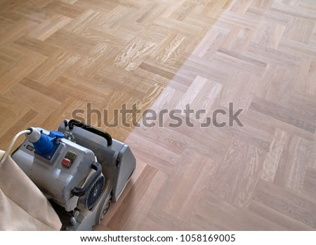 Sanding hardwood floor with the grinding machine. Repair in the apartment. Carpenter doing parquet wood floor polishing maintenance work by grinding machine Royalty-Free Stock Photo #1058169005