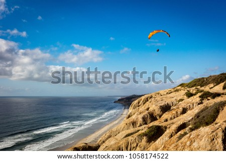 Gliders fly over the Black beach, in San Diego, California #1058174522