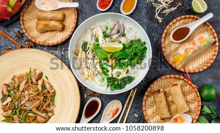 Assorted asian dinner, vietnamese food. Pho ga, pho bo, noodles, spring rolls Royalty-Free Stock Photo #1058200898