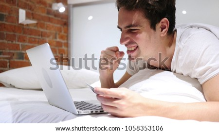 Man in Bed Excited for Successful Online Shopping, Transaction #1058353106