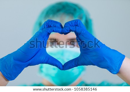 Young woman doctor with blue eyes wearing a cap and face mask showing hands in shape of love heart in front of face with gloves #1058385146