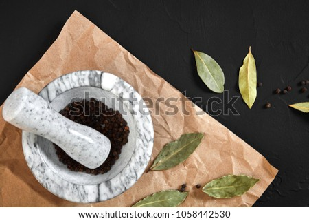 White mortar and pestle with dried peppers in flat lay on black background #1058442530