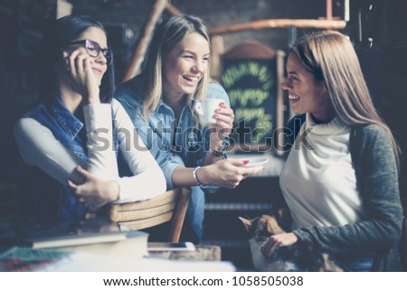 Cheerful three young girls sitting in cafe and having conversation. One girl talking on phone. #1058505038