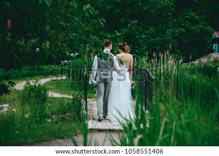the bride and groom posing for a wedding walk. rustic wedding concept #1058551406