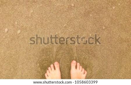 Vacation on ocean beach, female feet on sea sand,  with a wave's edge. Beach travel - woman stands on sand beach #1058603399