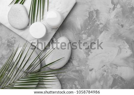 Spa stones and leaves on grey background Royalty-Free Stock Photo #1058784986