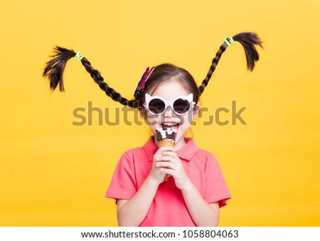 smiling little girl eating ice cream #1058804063