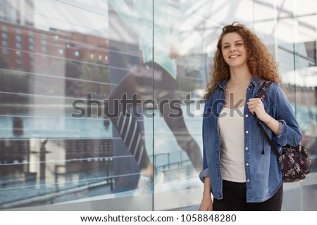 Adorable lovely glad young female with curly hair, wears fashionable denim jacket and carries rucksack, comes in shopping centre for buying new clothes and products, enjoys spare time or weekend #1058848280