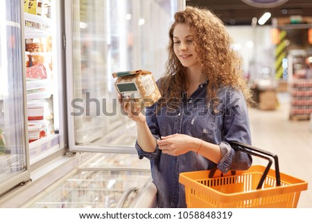 Beautiful young female with pleased expression, holds shopping cart, reads information abpput product, stands near fridge in supermarket, chooses necessary items for preparing delicious dinner #1058848319