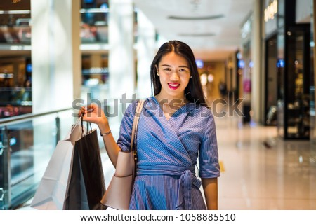 Happy Asian girl doing shopping in the mall #1058885510
