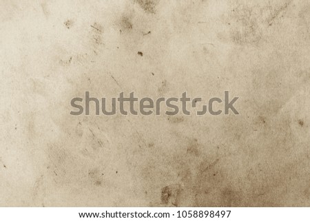 Blank aged paper sheet as old dirty frame background with dust and stains. Front view. Vintage and antique art concept. Detailed closeup studio shot. Toned #1058898497
