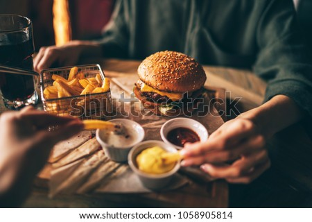 Group of friends eating at fast food. Friends are eating burgers while spending time together in cafe.Tasty grilled beef burger with lettuce and mayonnaise served on pieces of brown paper. #1058905814