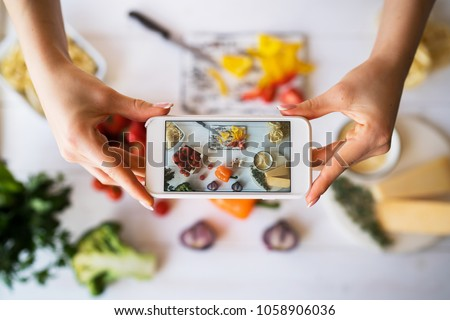 Food blogger concept. Young woman recording video on smartphone at kitchen. Woman recording every step of cooking process for her blog. Diet, technology, health, food, cooking, culinary, and people. #1058906036