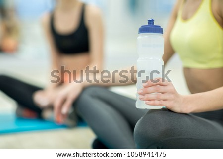 Plastic bottle with water in hand of cross-legged woman sitting on the floor during break after workout in gym #1058941475