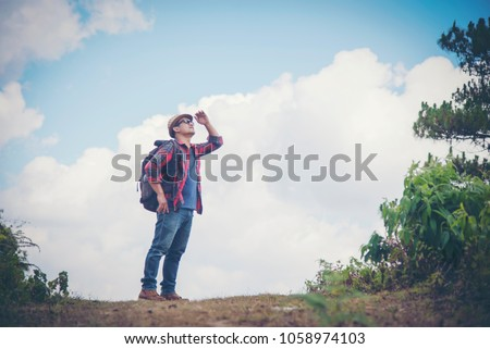 Young Man Traveler with map backpack relaxing outdoor with rocky mountains on background Summer vacations and Lifestyle hiking concept #1058974103