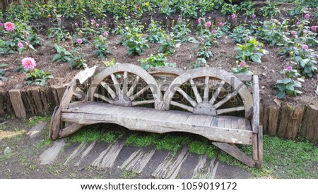 Wooden bench which made from the old cart wheel in the flower row of the botanical garden. #1059019172