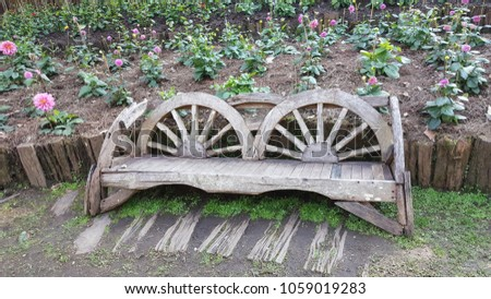 Wooden bench which made from the old cart wheel in the flower row of the botanical garden. #1059019283