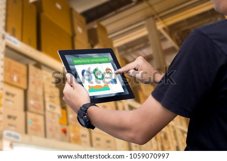 Smart warehouse management system.Worker hands holding tablet on blurred warehouse as background #1059070997