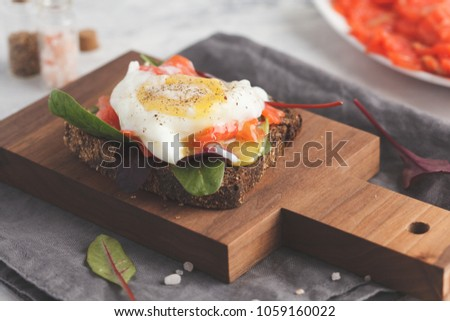 Fresh sandwich with egg poached, red fish on rye bread. Keto-balanced diet food. #1059160022