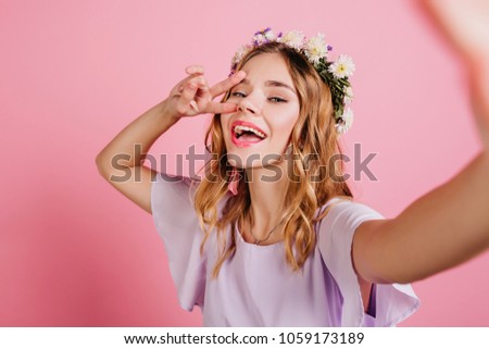 Inspired fair-haired girl in purple attire spending time in studio. Close-up portrait of lovable blonde lady in flower wreath making selfie and laughing. #1059173189