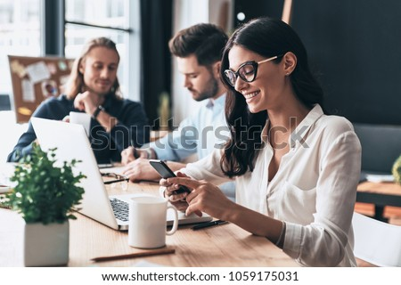 Young coworkers. Young modern colleagues in smart casual wear working while spending time in the office #1059175031
