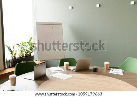 Conference table with laptops and chairs in empty meeting room with nobody, modern company office boardroom interior with flip chart for daily work and corporate team group business briefings concept Royalty-Free Stock Photo #1059179663