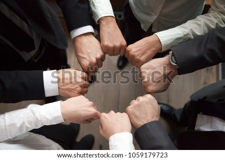 Business team or partners put fists in circle as concept of motivating engaging teambuilding activity, reliable support, help in cooperation, trust unity in collaboration teamwork, close up top view #1059179723