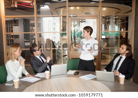 Businesswoman presenting document or speaking about new business project results at group meeting, female manager holding contract making sales offer to investors or clients explaining deal benefits Royalty-Free Stock Photo #1059179771