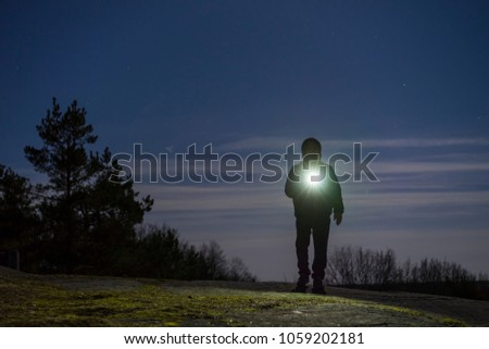 Human standing outdoor at night with flashlight and hoodie on head. Male man standing in Swedish Scandinavian nature and landscape shining with torch. Calm, peaceful photo. Mystical abstract image. Royalty-Free Stock Photo #1059202181