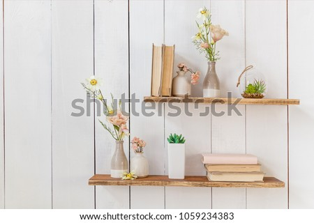 Old books and flowers in a vase on a wooden shelf, frame with flowers on a wooden wall. Wooden shelves with books and flowers on the wall #1059234383