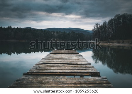 Mole (pier) on the lake.  Wooden bridge in forest in spring time with blue lake. Lake for fishing with pier. Dark and  Foggy lake with hills. #1059253628