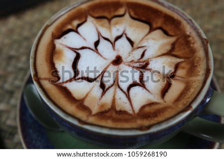 Closed up Hot coffee Latte beautiful  flower art in ceramic mug vintage good design morning beverage aroma on wooden table background  #1059268190