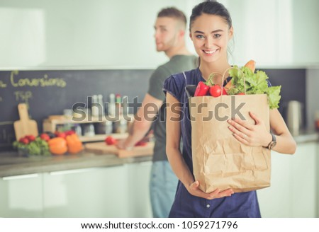 Young couple in the kitchen , woman with a bag of groceries shopping #1059271796