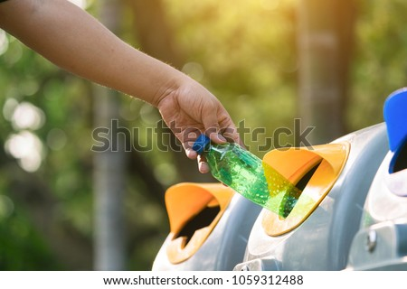 Close up hand throwing empty plastic bottle into the trash Recycling Concept #1059312488