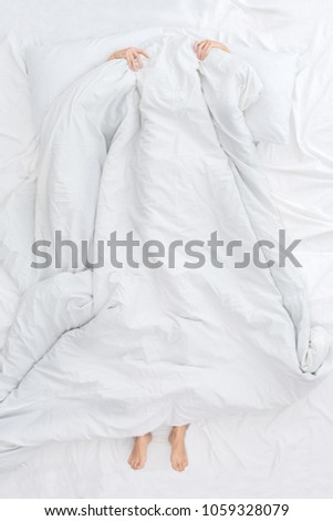 Young woman on bed top view morning concept hiding under blanket #1059328079