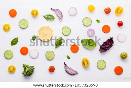 Food pattern with raw ingredients of salad. Various vegetables lettuce leaves, cucumbers, tomatoes, carrots, broccoli, onion and lemon flat lay on white background. #1059328598