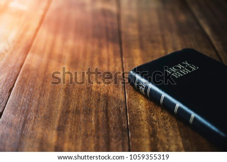 holy bible book, on wooden table on wooden table with window light in the morning, copy space