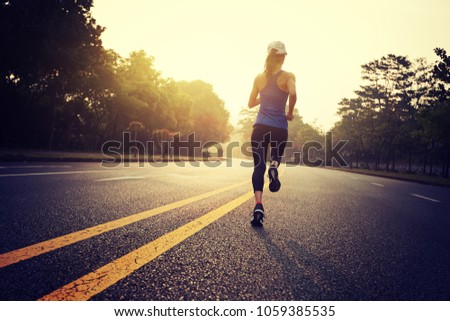 Fitness sportswoman running on sunrise trail #1059385535
