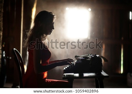 Silhouette of a beautiful girl in a red dress on the background of a window in an old house #1059402896