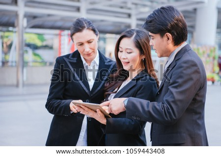Businessman and businesswoman looking tablet or laptop in modern city, Unity and teamwork concept. #1059443408
