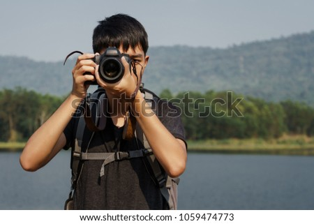 Young Asian backpack travelling. He use DSLR camara to take a photo.