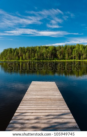 Wooden pier on lake symmetrical scene, vertical view with forest #105949745